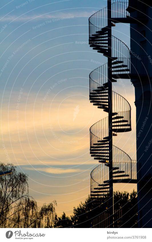 gewendelte Außentreppe an einem Gebäude vor schönem Abendhimmel. Wendeltreppe spiralförmig Spirale Geländer nach oben nach unten Architektur Wege & Pfade Treppe