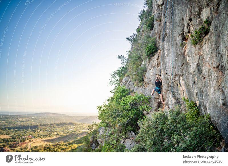 Mann klettert auf einen Felsen Klettern Portugal im Freien Park Natur hoch Aufsteiger aktiv Aktivität Adrenalin Abenteuer Algarve Mut Karabiner Herausforderung