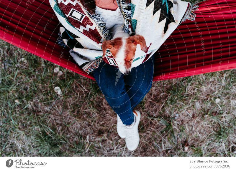 junge Frau entspannt sich mit ihrem Hund in orangefarbener Hängematte. Mit Decke zugedeckt. Zelten im Freien. Herbstsaison bei Sonnenuntergang
