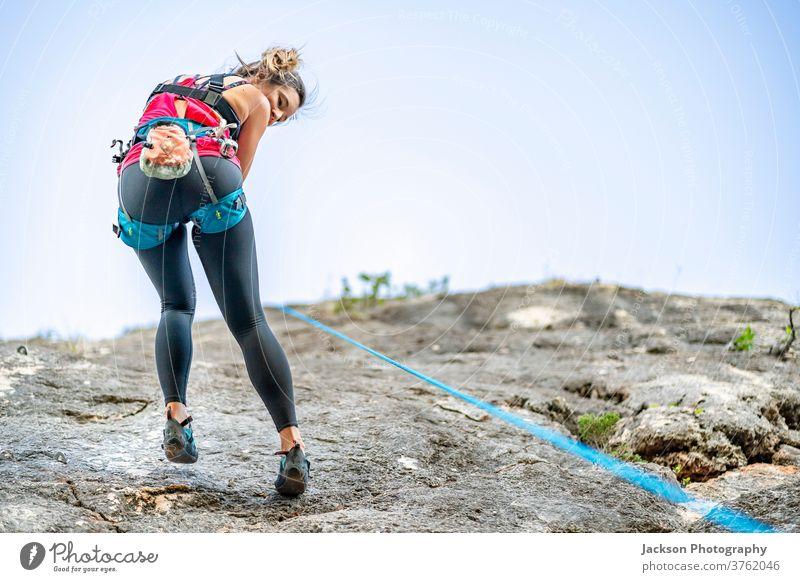Eine Frau klettert im Klettergurt an einem steilen Felsen Aufsteiger Klettern Kabelbaum nach unten aktiv Aktivität Adrenalin alkoholisch Algarve Klippe Aufstieg