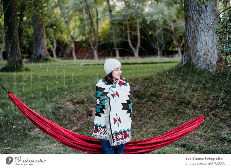 junge Frau, die mit der Decke bedeckt, die nahe bei der Hängematte steht. Herbstsaison. Camping-Konzept kalt im Freien Natur Sonnenuntergang orange Park