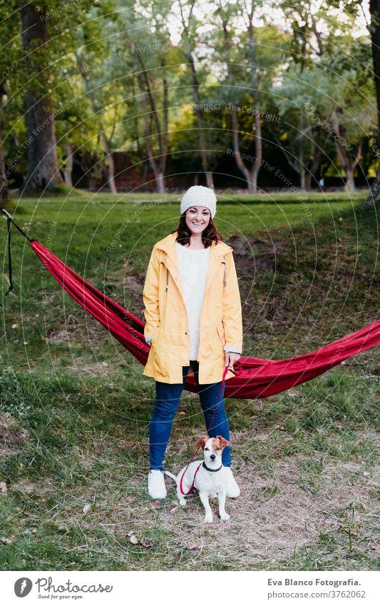 junge frau mit gelbem regenmantel steht neben der hängematte mit ihrem jack russell hund. herbstsaison. camping konzept Frau Hund liegende Hängematte Haustier