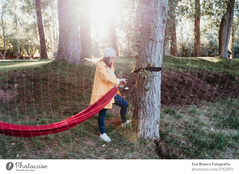 junge Frau mit gelbem Regenmantel, die eine Hängematte zur Entspannung vorbereitet. Camping im Freien. Herbstsaison Sonnenuntergang gelber Regenmantel orange