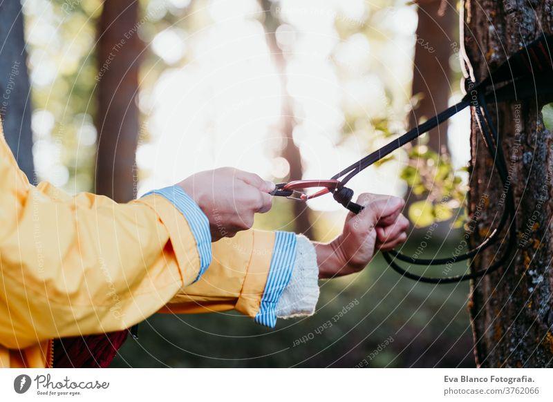 Nicht erkennbare Frau mit gelbem Regenmantel, die eine Hängematte zur Entspannung vorbereitet. Camping im Freien. Herbstsaison Sonnenuntergang