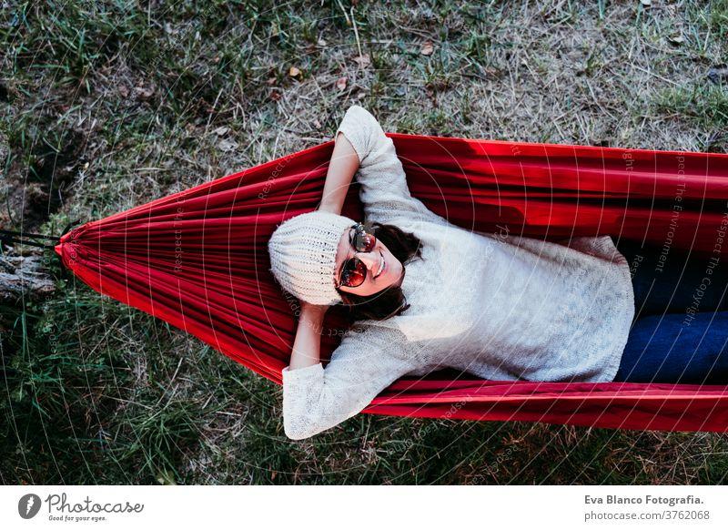 junge Frau entspannt sich in orangefarbener Hängematte. Zelten im Freien. Herbstsaison bei Sonnenuntergang Lügen Natur Park Kaukasier vorbereitend