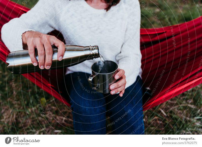 junge Frau hält Thermoskanne, gießt Wasser in Metallbecher, entspannt sich bei Sonnenuntergang in der Hängematte. Herbstzeit unkenntlich Fuß Lügen im Freien