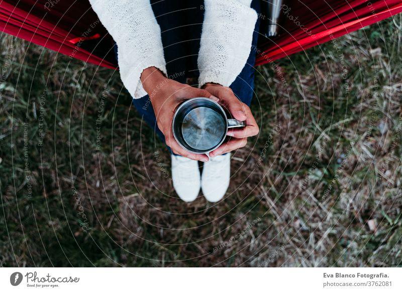Draufsicht einer Frau, die bei Sonnenuntergang in der Hängematte entspannt und einen Becher Wasser aus Metall hält. Thermoskanne unkenntlich Fuß Lügen Herbst