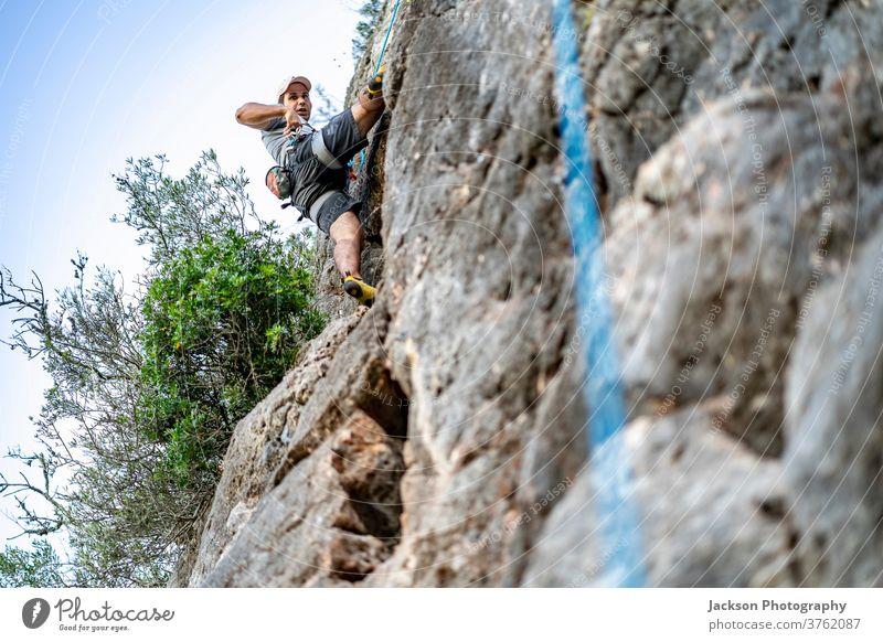Ein Mann klettert mit einem Klettergurt auf einen Felsen Aufsteiger Klettern Portugal Abenteuer im Freien Park Natur hoch aktiv Aktivität Adrenalin Algarve Mut
