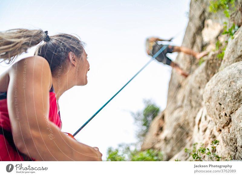 Bergsteiger sichert einen weiteren Bergsteiger beim Abstieg Kletterer Klettern Felsen nach unten gehen Sicherung Lifestyle absteigend herunterkommen sicheres