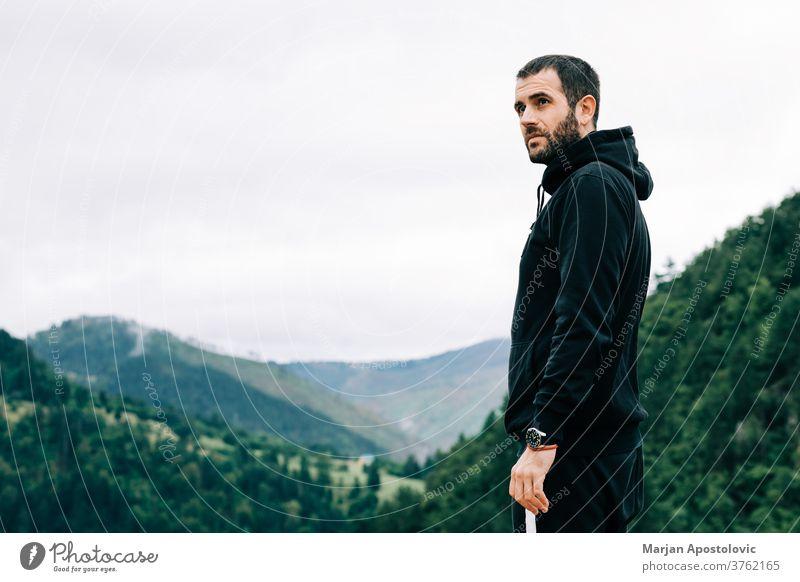 Junger männlicher Naturforscher geniesst die Aussicht auf op des Berges Erwachsener Abenteuer allein bärtig lässig Kaukasier wolkig Landschaft Morgendämmerung