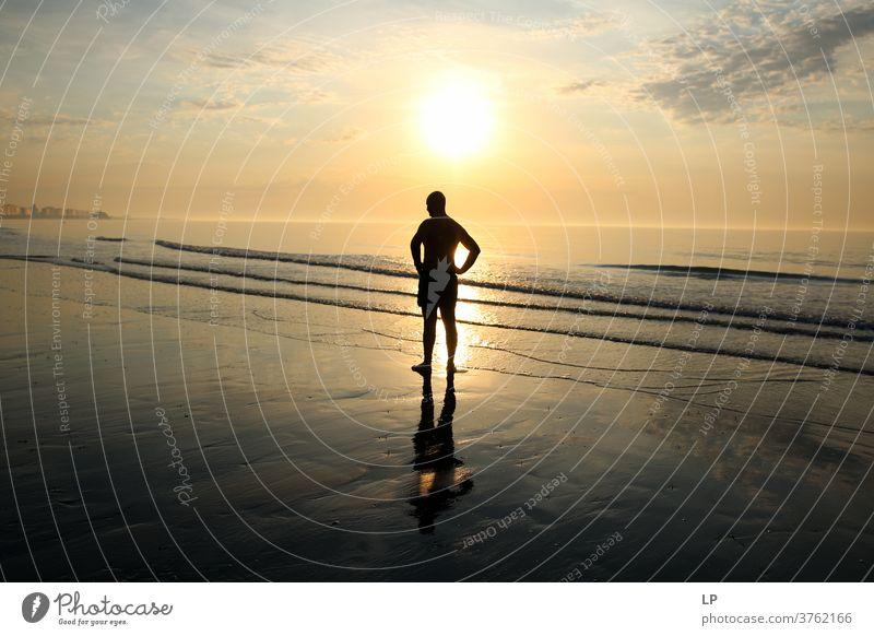 Mann, der am Meeresufer gegen die Sonne steht Führung Anleitung Regie Freiheit Freizeit & Hobby Sonnenuntergangsstrand Sonnenuntergangshimmel