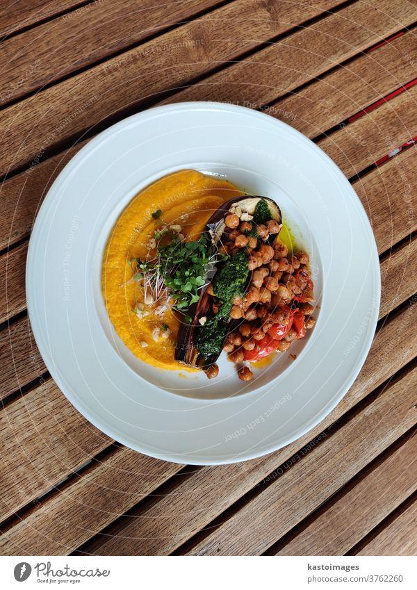 Gesundes veganes Gericht aus Auberginen, Kichererbsen- und Zucchinipüree, Pesto, Kirschtomaten und frischen Kräutern. Veganer Speise Püree Pesto-Kirschtomaten