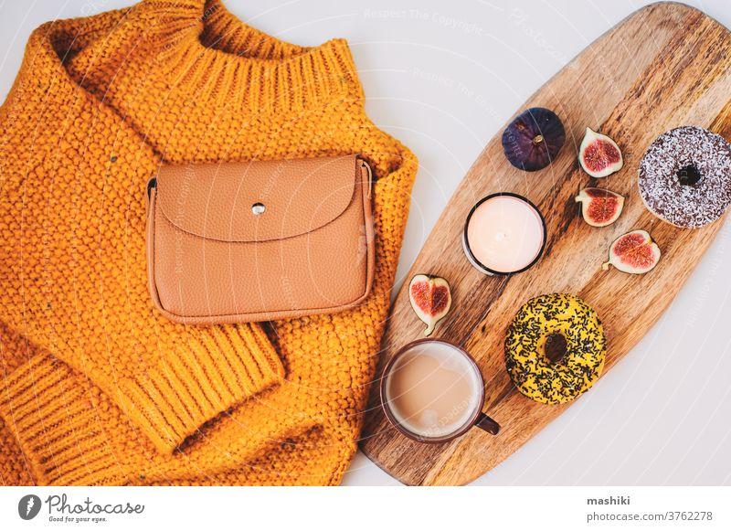 gemütliche Herbstmorgen-Flachlegerkomposition mit warmem Pullover, Tasse Kaffee, süßem Donut zum Frühstück und Modehandtasche fallen Winter Morgen