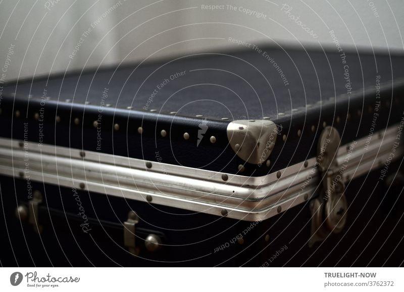 Eleganter Übersee Koffer aus dunkelblauem Leder und Kunststoff mit matten und glänzenden Beschlägen aus Aluminium zur Verstärkung, Tragegriffen und abschließbaren Verschlüssen in diagonaler Perspektive vor hellgrauem Hintergrund