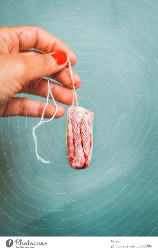 Kein Tabu - Eine weibliche Hand hält einen blutigen Tampon. Menstruation echt Blut Zyklus rot natürlich Realität blutiger Tampon vollgeblutet blutend