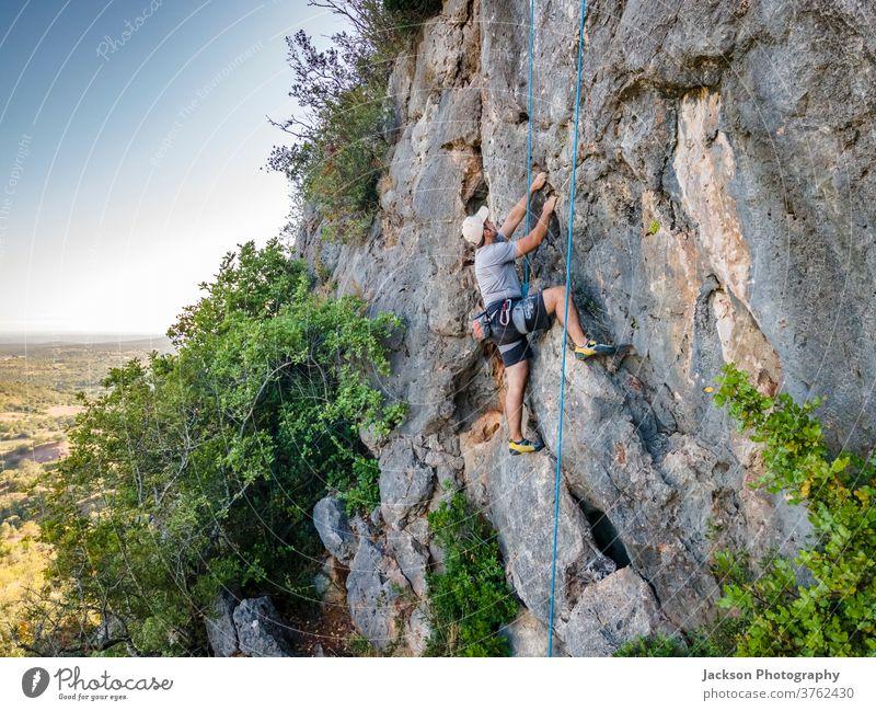 Bergsteiger mit Klettergurt auf riesigem Felsen Sport Aufsteiger Klettern Mann aktiv Aktivität Adrenalin Abenteuer Algarve Mut Karabiner Herausforderung Klippe