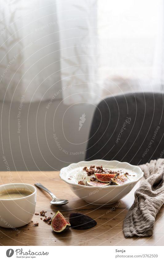 Gedeckter Frühstückstisch mit Granola, Joghurt und frischen Feigen und eine Tasse Kaffee. Fensterlicht, Morgensonne. Schüsseln Tisch Sessel zuhause Hygge