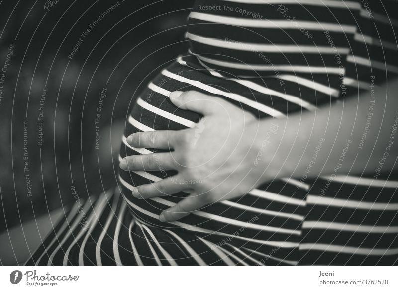 Hand einer Frau - einer werdenden Mutter - fühlt den Babybauch Schwangerschaft schwanger Bauch dick Kugel Geburt Babybauchshooting schön schwarzweiß