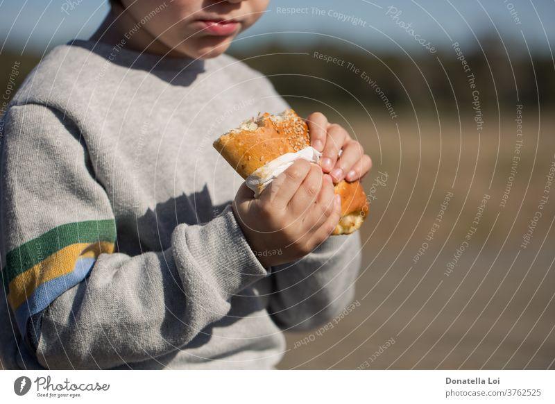 Kind isst Sandwich im Freien Appetit & Hunger Amuse-Gueule Junge Brot Frühstück calzone Kohlenhydrat Kaukasier Nahaufnahme lecker essen Essen schnell Fast-Food