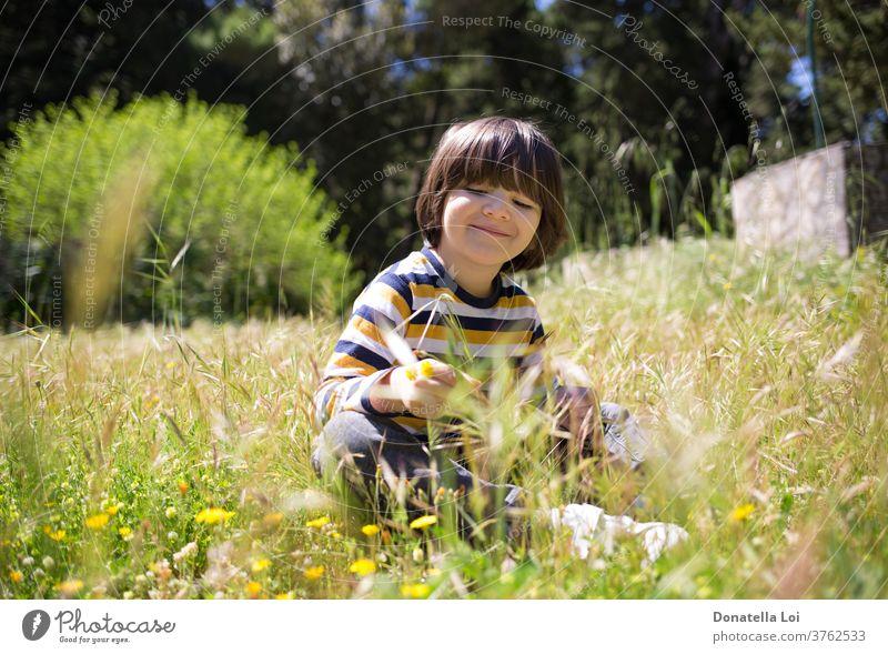 Kind auf dem Feld sitzend Junge Kaukasier Kindheit Landschaft Tag Gesicht Blume Blumen Spaß Garten Gras grün Fröhlichkeit Glück Gesundheit Beteiligung Feiertage
