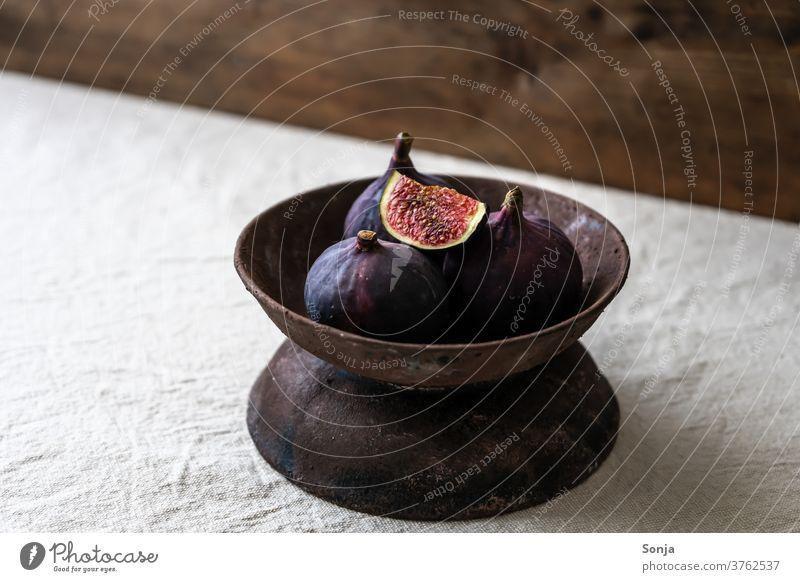Frische Feigen in einer rustikalen Schüssel auf einem beigen Leinen Tischtuch. schüssel obstschale Obst frisch roh Gesundheit reif organisch natürlich Diät Holz