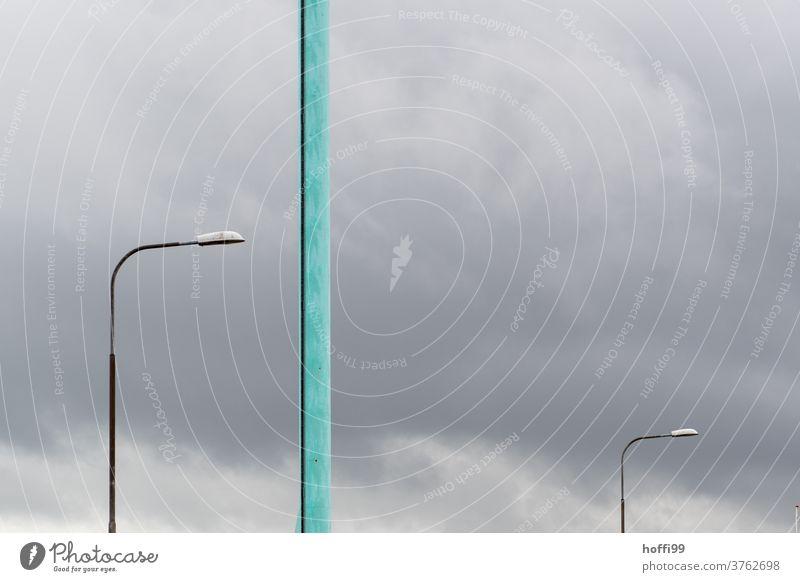 zwei Lampen und ein türkiser Pfahl vor grauem Himmel - ein Sturm kommt auf Straßenlampe Peitschenlampen minimalistisch Farbfoto stürmisch stürmische zeiten