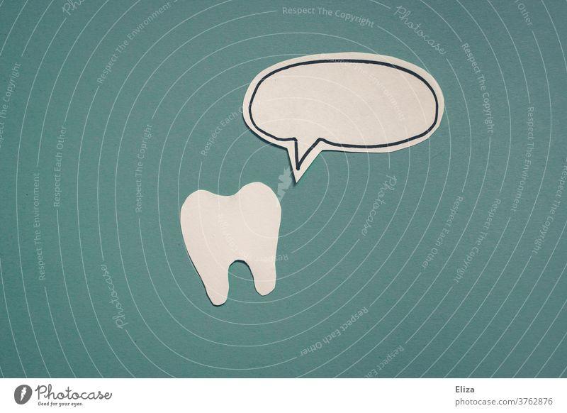 Ein Zahn und eine Sprechblase aus Papier auf blauem Hintergrund Zahnarzt Zahnhygiene Zahnmedizin dental Zähne Zähneputzen Kommunikation sprechend weiß
