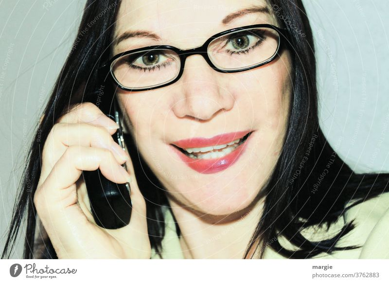 Eine Frau mit Brille beim telefonieren Junge Frau feminin Frauengesicht Telefon Telefongespräch Telefonhörer Handy Brillenträgerin Callcenter Geschäftsfrau