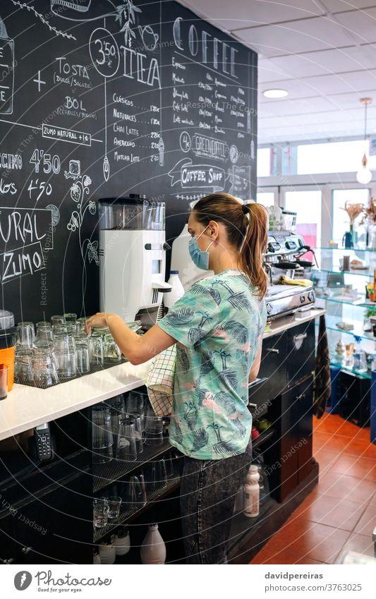 Kellnerin mit Maskenreinigungsbrille Platzierung Reinigen Brille Küchenhandtücher Gesichtsmaske Coronavirus Geschriebene Tafel Kaffeemaschine Überprüfung von