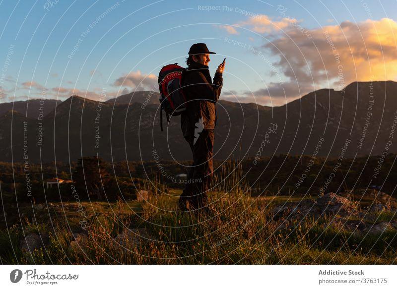Männlicher Reisender, der in den Bergen mit seinem Smartphone spricht Wanderer sprechen Mann Sonnenuntergang Berge u. Gebirge bewundern benutzend Hochland