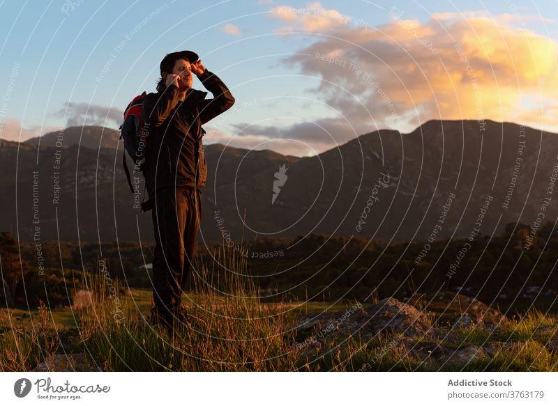 Männlicher Wanderer mit Rucksack im Hochlandtal Reisender Hügel Mann Berge u. Gebirge bewundern Tal erkunden Sonnenuntergang Himmel Urlaub Kamm Landschaft