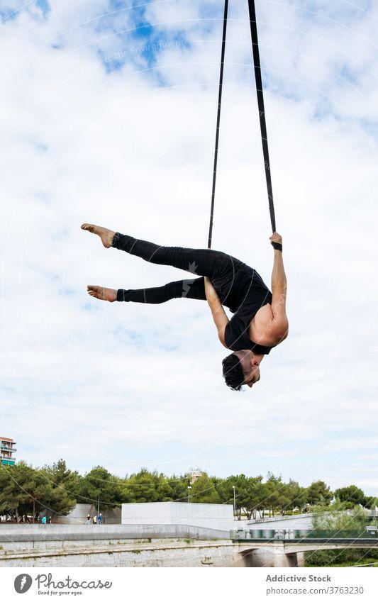 Flexibler Mann trainiert an Traggurten Antenne Gurt Turner Training gymnastisch hängen ausführen beweglich passen Park männlich Übung Energie Athlet Sport
