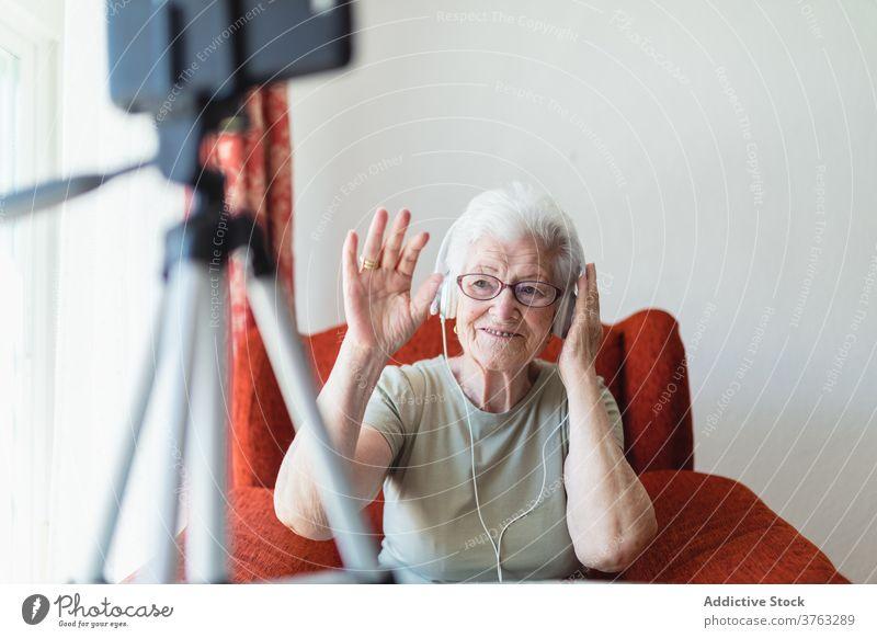 Ältere Frau mit Videoanruf mit Kopfhörern Senior zuhören Musik älter Gesang genießen sich[Akk] entspannen heimwärts Freude Armsessel gemütlich sitzen Komfort