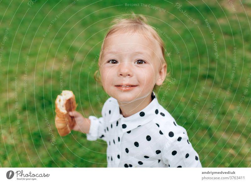 Süßes und lustiges kleines Mädchen mit Brötchen in der Hand und lächelnd vor einem diffusen grünen Grashintergrund. selektiver Fokus niedlich Kind Freude Spaß
