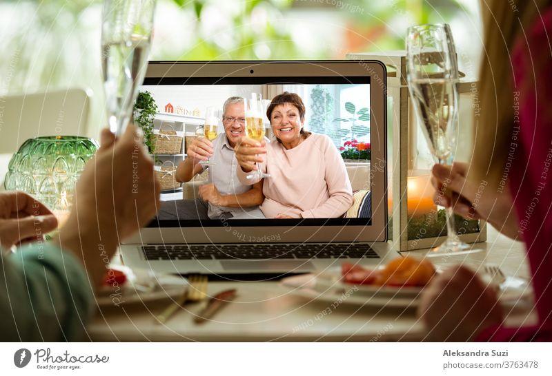 Mann und Frau sitzen am Esstisch, essen zu Abend, trinken Champagner und führen Videogespräche mit älteren Eltern am Laptop. Zu Hause bleiben, Quarantäne und soziale Distanzierung bei der Feier des Ereignisses.