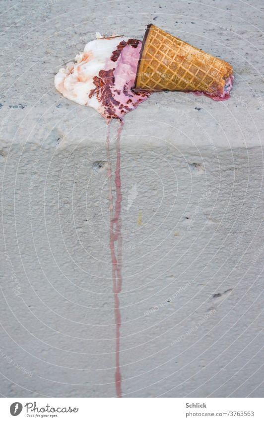 Speiseeis in angebissener Waffel schmilzt auf einer grauen Mauer achtlos dahin schmelzen Sommer Eis Kunstwerk fließen zerfließen weggeworfen liegen Hitze rosa
