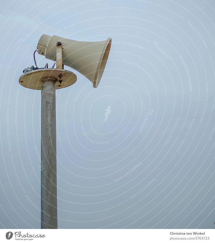 Seitenansicht eines älteren Lautsprechers in Form eines Megaphons vor bläulich diesigem Himmel Megafon Mast Durchsage Kommunizieren Information Warnung