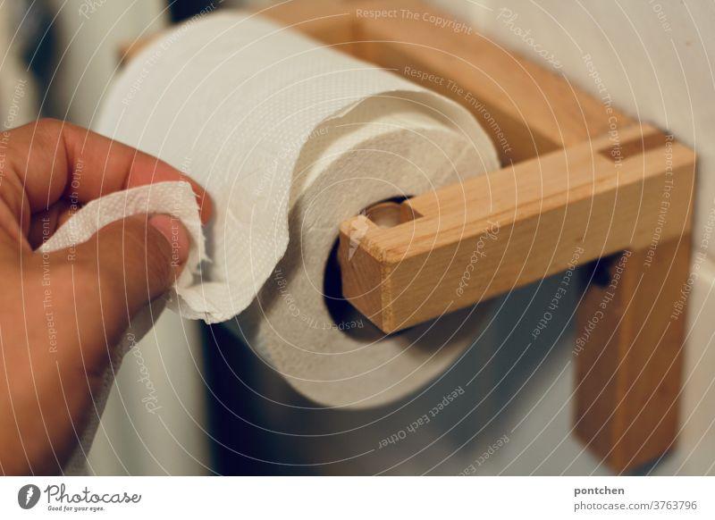 Hand reißt Klopapier ab. Toilettenpapier, Toilettengang. klopapier Rolle Klopapierrolle klogang abreissen hand badezimmer Körperpflege Fliesen u. Kacheln