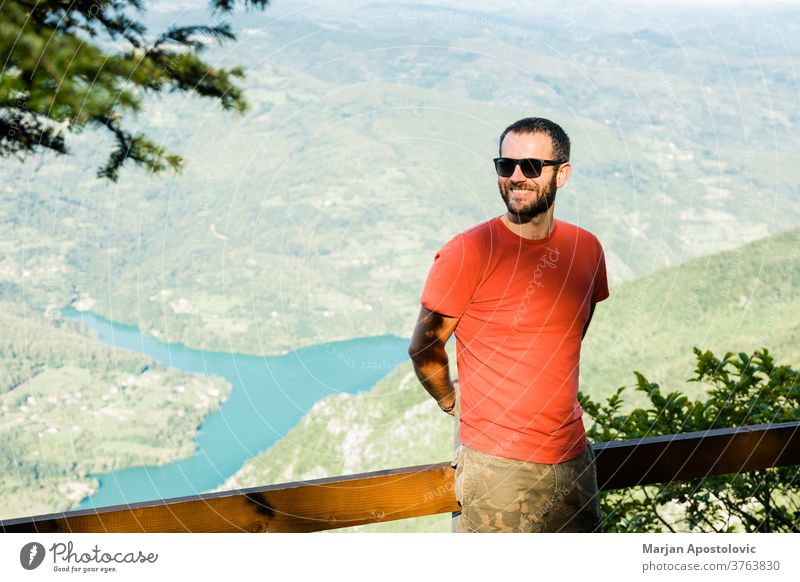 Junger Mann in den Bergen mit Blick auf den See Abenteuer allein Hintergrund schön Schlucht Kaukasier Tag Saum genießend erkunden Entdecker frei Freiheit Typ