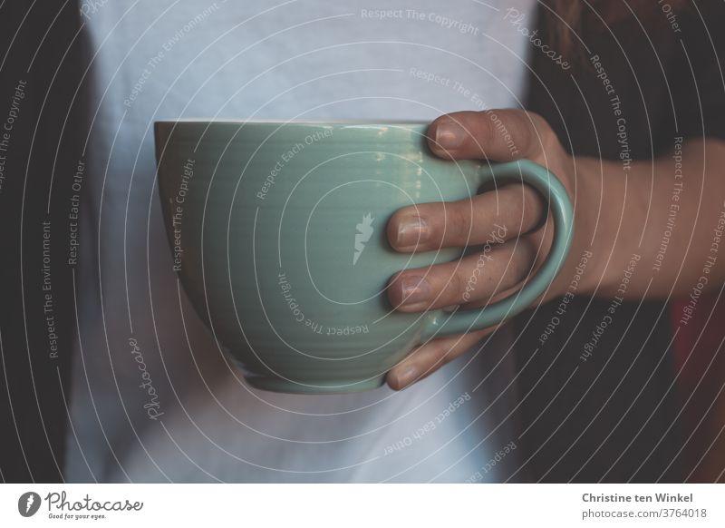Teebecher oder Kaffeebecher gehalten von der Hand einer jungen Frau. Nahaufnahme mit natürlichem Fensterlicht Teetasse Heißgetränk Kaffeetasse haltend
