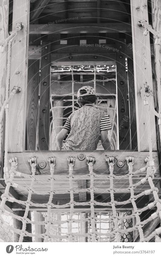 Junge auf einem Spielplatz mit Holzkonstruktion und Seilnetz Spielset Klettern Aufstieg erkunden Kind Seile Strickleiter Netz hölzern Schulpause spielen Spielen