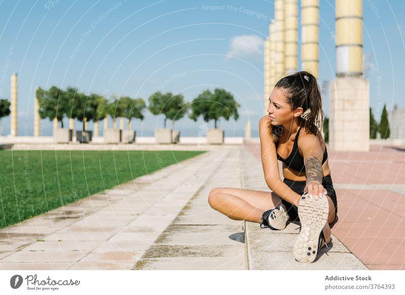 Weibliche Läuferin bindet die Schnürsenkel vor dem Training auf der Straße Sportlerin Krawatte Schuhbänder Turnschuh Übung urban Athlet passen Frau vorbereiten