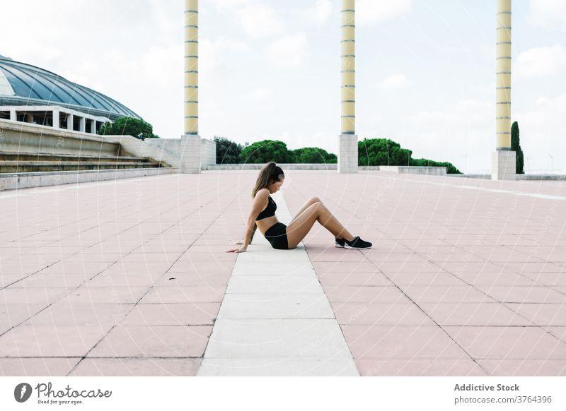 Fitte Frau in Sportkleidung ruht sich nach dem Training auf dem Stadtplatz aus passen ruhen sich[Akk] entspannen Straße Pause Fitness urban Erholung müde Übung