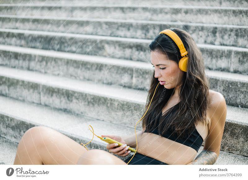 Seriöse Sportlerin beim Musikhören auf der Treppe Smartphone Kopfhörer zuhören ruhen Training Apparatur Athlet Frau benutzend Mobile Telefon Gerät
