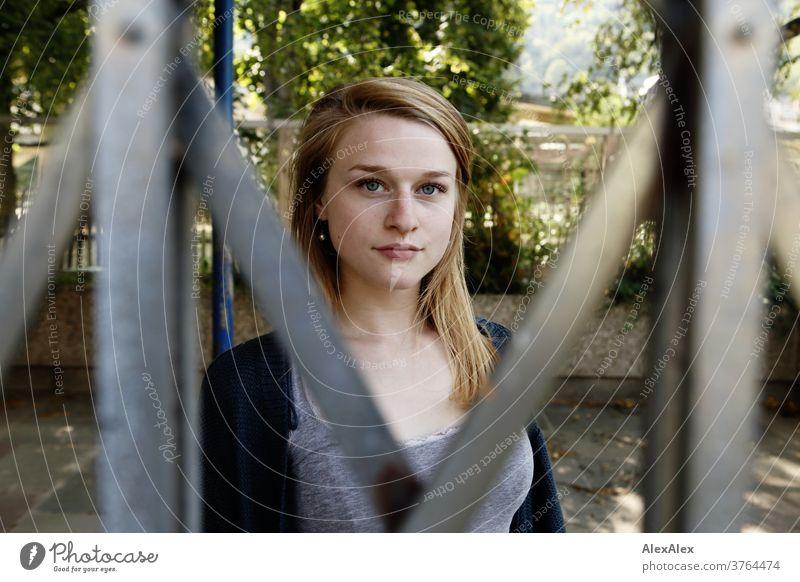Nahes Portrait einer jungen Frau, die hinter einem Schiebegitter steht und hindurch blickt junge Frau schlank schön athletisch blond 18-25 Jahre rotblond Haare
