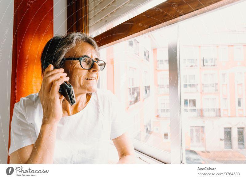 Nahaufnahme einer alten Frau, die mit dem Handy telefoniert und lächelnd durch das Fenster schaut Großmutter im Innenbereich Ruhestand Person Mitteilung