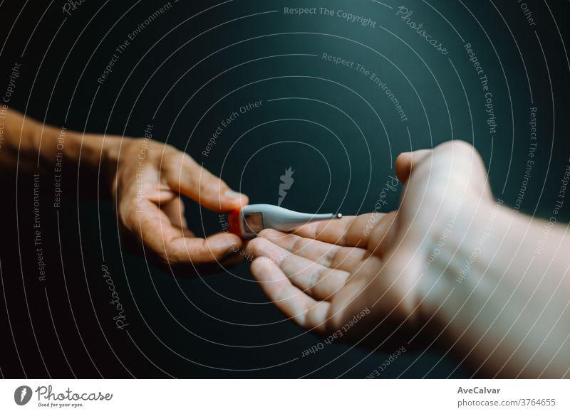 Ein alter Hase gibt einer jüngeren Hand ein Thermometer Grippe Schmerz Krankheit Hemd krank gutaussehend Schmerzen Virus müde Gesundheitswesen Menschen