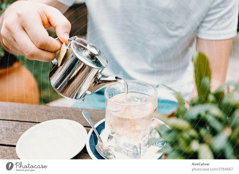 Junger Mann serviert einen Eistee in einer modernen Bar trocknen schließen Tee Kraut erwärmen vereinzelt Gesundheit Asien trinken Teetasse Frühstück Hand Gießen
