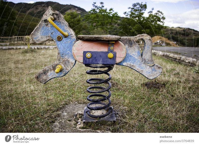 Verlassenes Schaukelpferd auf Spielplatz weiß Antiquität einsam vereinzelt Mitfahrgelegenheit Freude Anziehungskraft hölzern Frühling Kindergarten Wippe