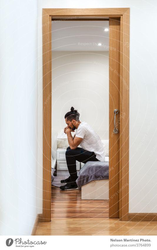 Hispanischer Mann isoliert in einem Raum. Er sieht nachdenklich aus. gestresst 1 Problematik Schmerz Verlust Stock im Innenbereich dunkel Lifestyle Sorge Opfer